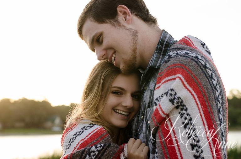 engagement couple, lake, couple, sunrise, embrace, hug, smile, blanket