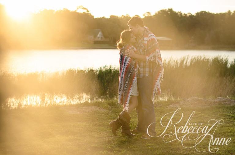 engagement couple, lake, couple, sunrise, embrace, hug, smile, blanket, sun, flares