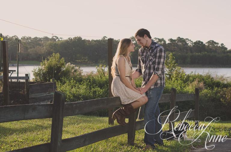 woman, girl, engagement couple, couple, lake, sunrise, embrace, hug, smile, flare, fence, dog