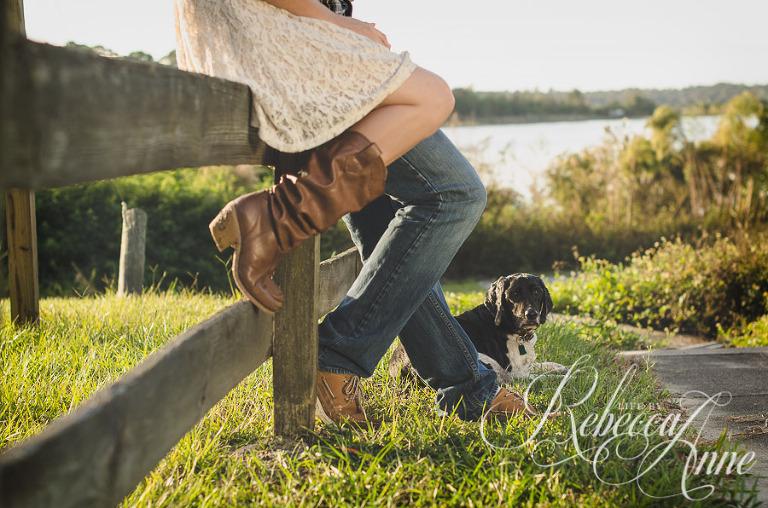 woman, girl, engagement couple, couple, lake, sunrise, embrace, hug, smile, flare, fence, dog, boots,