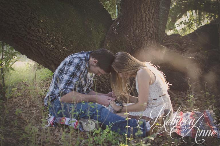 woman, girl, engagement couple, couple, embrace, hug, smile, man, boy, bible, reading, reading bible, country, blanket, pasture, praying, pray